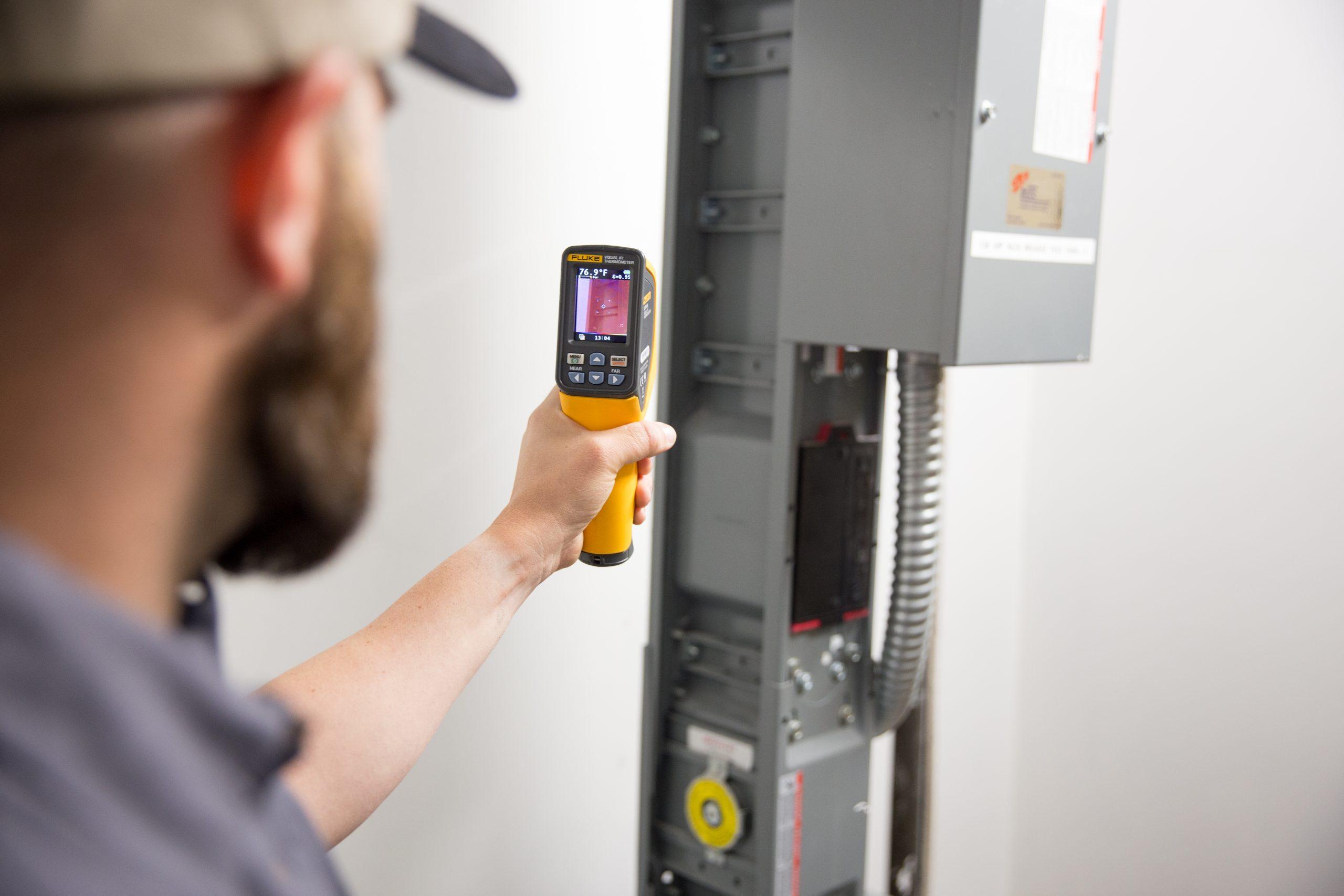 technician using FLIR on electrical panel